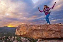 Hiker teen girl selfie phone on peak of mountain. Hiker teen girl selfie smartphone on peak of mountain at sunset royalty free stock photo