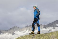 Hiker is thinking about the meaning of life. In the Swiss Alps Stock Photo