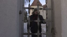 Hiker throws open the gates near the medieval castle stock video footage