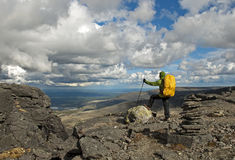 Hiker on the top. Hiker with backpack and trekking pole on the top of the mountain, Russia, Hibiny Stock Photo