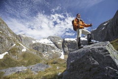 Hiker On Top Of Boulder In Mountains Stock Images
