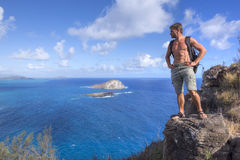 Hiker on top of mountain in Hawaii Stock Photo