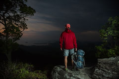 Hiker on top of the mountain. Hiker standing on top of the mountain and enjoying twilight valley view Stock Photo