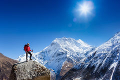 Hiker at the top of a rock with backpack enjoy sunny day Stock Photos