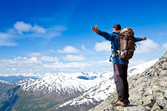 Hiker at the top of a rock with his hands raised Royalty Free Stock Image