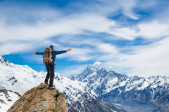 Hiker at the top of a rock with his hands raised enjoy sunny day Stock Images