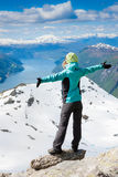 Hiker at the top of a rock with his hands up Stock Image