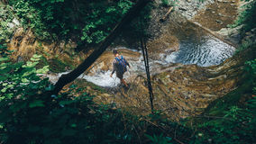 Hiker Traveler Explorer Crosses Wild River Waterfall Support Exercise Extreme Sports Concept. Hiker Traveler Explorer Cross Wild River Waterfall Support Exercise Stock Photo