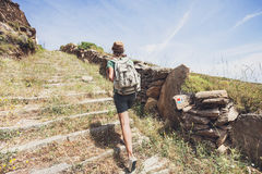 Hiker traveler girl on a hiking trail, travel and active lifestyle concept. Hiker traveler girl walking on a hiking trail Royalty Free Stock Photos