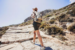 Hiker traveler girl on a hiking trail, travel and active lifestyle concept. Hiker traveler girl walking on a hiking trail Royalty Free Stock Image