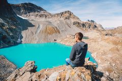 Hiker traveler at the mountain lake. Turquoise lake in the mountains. Hiker traveler at the mountain lake. Turquoise lake in the mountain Stock Images