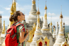Hiker traveling  with backpack and looks at Buddhist stupas. Bir Royalty Free Stock Image