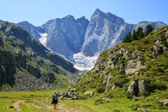 Hiker on a trek in the national park Pyrenees.Occitanie in south of France. Hiker on a trek in the national park Pyrenees. Mountain Vignemale in the background royalty free stock images