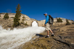Hiker treking along cascades. Stock Photo