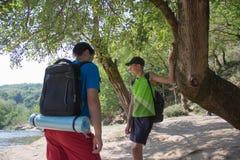 Hiker trekking на следе в туристах группы леса исследуя природу идя через древесины Стоковые Изображения RF