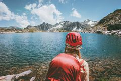 Hiker trekking at blue lake in mountains Travel Lifestyle adventure concept. Summer vacations outdoor exploring wild nature wearing helmet Royalty Free Stock Photography