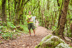 Hiker trekking with map in forest