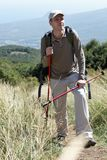 Hiker in mountains. Hiker with trekking poles and backpack on a mountain footpath Stock Image