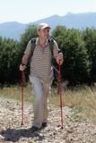 Hiker in mountains. Hiker with trekking poles and backpack on a mountain footpath Royalty Free Stock Image
