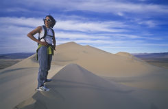 Hiker trekking on sand dunes. Royalty Free Stock Image