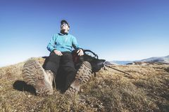 Hiker in trekking shoes rests on the top of a mountain. Selective focus on a shoe sole royalty free stock image