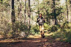 Man walking in forest wearing a backpack. Hiker trekking on the trail in a forest. Man exploring nature walking through the woods Stock Photos