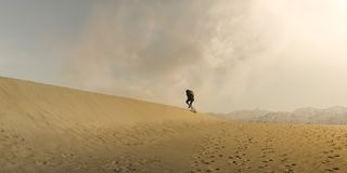 Hiker Trudging through desert sand dunes in Death Valley National Park. Early morning sunshine and clouds dispersed. Landscape shot royalty free stock photos