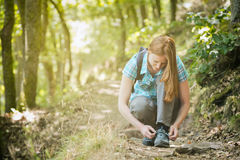 Hiker Tying Her Shoe on a Trail Royalty Free Stock Photography