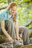 Hiker Tying Shoelaces in a Forest Stock Image