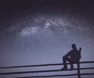 Hiker under the starry sky. Instagram stylization. Hiker sitting on a wooden fence under the starry sky with milky way. Fairy night. Instagram stylization Royalty Free Stock Photography