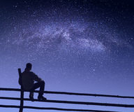 Hiker under the starry sky. Hiker sitting on a wooden fence under the starry sky with milky way. Fairy night Royalty Free Stock Photos