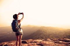 Hiker use digital camera taking photo at mountain peak cliff Stock Photos