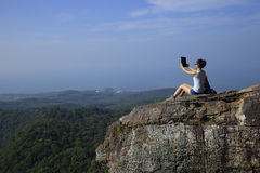 Hiker use digital tablet at mountain peak cliff Royalty Free Stock Photos