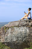 Hiker use digital tablet at mountain peak cliff Stock Images