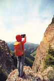 Hiker use digital tablet taking photo on mountain peak cliff Stock Image