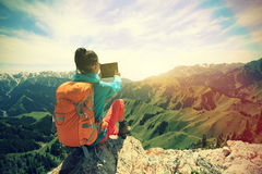 Hiker use digital tablet taking photo on mountain peak cliff Stock Photo