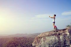 Hiker use digital tablet  taking photo at mountain peak cliff Royalty Free Stock Image