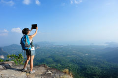 Hiker use digital tablet taking photo at mountain peak cliff Royalty Free Stock Photography