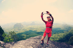 Hiker use smartphone taking self photo on seaside mountain top. Young woman hiker use smartphone taking self photo on seaside mountain top Royalty Free Stock Image