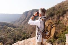 Hiker using binoculars. Middle aged male hiker using binoculars on top of the mountain stock photo