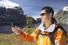 Hiker Using Compass By Mountain Lake Stock Image