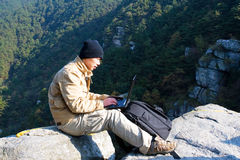 Hiker using a laptop outdoors Royalty Free Stock Photography