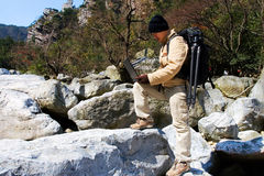 Hiker using a laptop outdoors Stock Photos