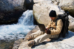 Hiker using a laptop outdoors Royalty Free Stock Images