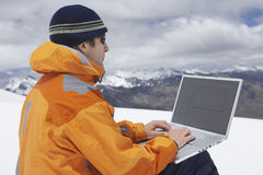 Hiker Using Laptop On Snowy Mountain Landscape Royalty Free Stock Images