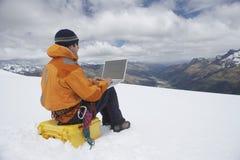 Hiker Using Laptop On Snowy Mountain Landscape Stock Photo