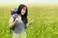 Hiker using smartphone on blossom meadow Royalty Free Stock Image