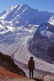 Hiker viewing glacier. Hiker viewing Gorner Glacier in snowy mountains above Zermatt, Switzerland Royalty Free Stock Photography