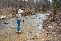Hiker walking across a stream. Royalty Free Stock Images