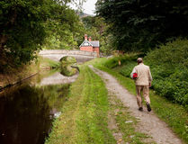 Hiker walking along canal in Shropshire. Solitary hiker alongside a calm canal approaching a stone bridge stock photos
